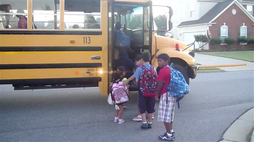 4 children loading a school bus